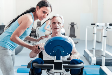 I support you. Determined old grey-haired man exercising on a training device while a smiling young dark-haired afro-american woman standing near him and they looking at the device