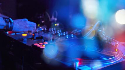 Closeup Dj playing at disco progressive electric music on a beautiful bokeh.