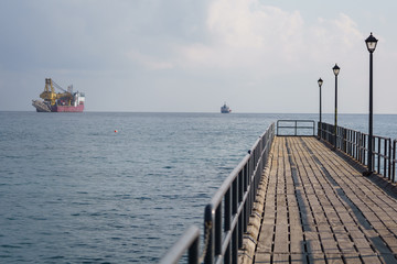 Photo of sea with floating cargo ship, wooden pier
