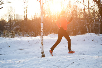 Photo of sports woman on run through winter forest
