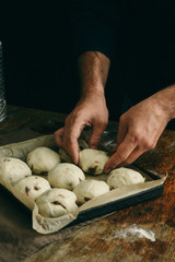 Fototapete - Man is cooking Easter cross buns in home kitchen