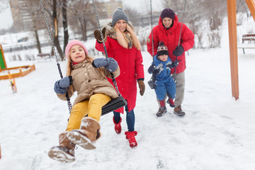 Picture of girl and boy swinging in winter in park with parents