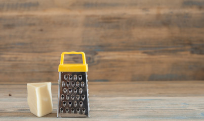 steel grater and cheese on wooden board