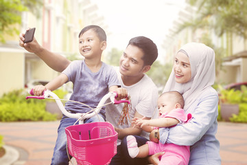 Happy muslim family taking self portrait outdoors