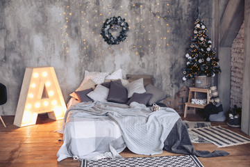 Luxurious bed in the New Year's interior with a Christmas tree and other decorations