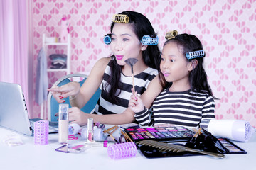 Mother and daughter with hair curler watching how to make-up tutorial