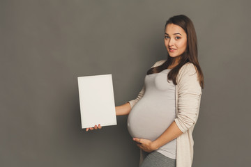 Young pregnant woman with blank white paper