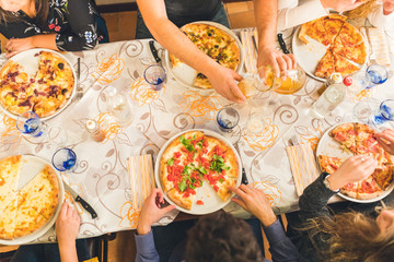 Group of friends eating pizza together at restaurant
