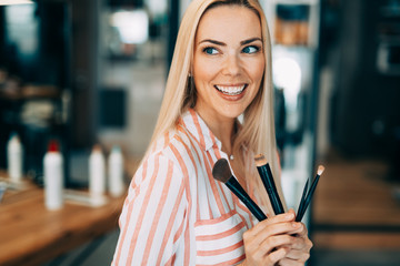 Portrait of the beautiful woman with make-up brushes