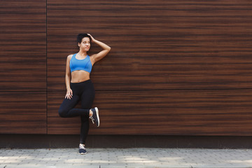 Sporty woman leaning on wooden wall, copy space
