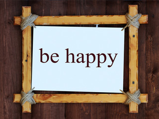 Wood frame on wooden background. The inscription, be happy