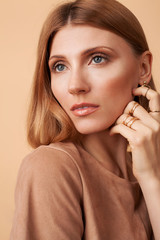 Fashion portrait of a beautiful girl with a natural make-up on a beige background in a beige dress with hand in gold rings