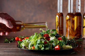 Green salad with olive oil pouring from a small bottle.