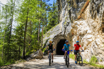 Mountain biking family with bikes on track, Cortina d'Ampezzo, Dolomites, Italy