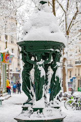 Snow covered public Wallace fountain in Paris