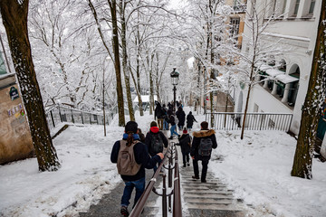 Tourists walking on snow covered stairs in Montmartre