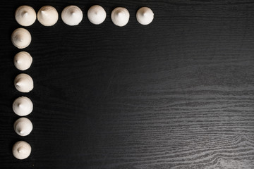 delicious merengues on the wood black background