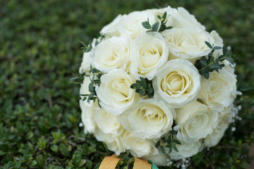 White rose flower bouquet in bundle shape for bridal in wedding ceremony on green grass