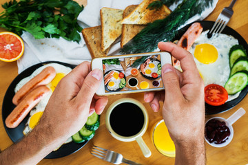 Male hands take a picture of an American breakfast on the phone top view. Food blogger