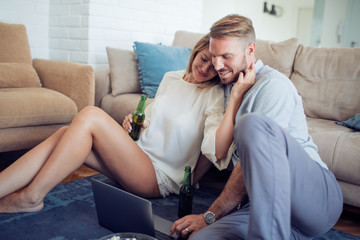 Young couple watching movie on laptop.