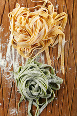 Two types of handmade italian tagliatelle pasta: classical one and green one with spinach