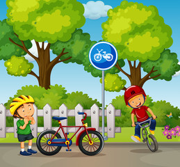 Two boys riding bike in the park