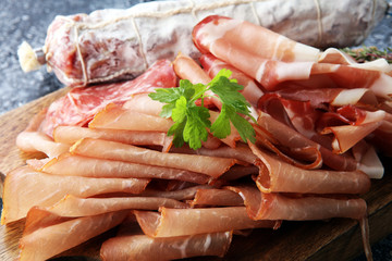 Food tray with delicious salami, pieces of sliced ham, . Meat platter with selection.