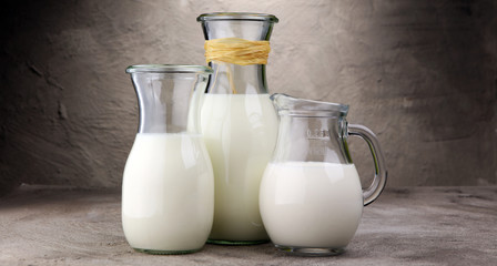 A jug of milk and glass of milk on a table