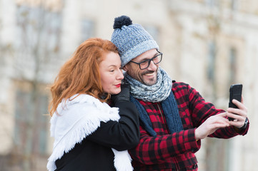 Couple of tourists makes selfy on smart-phone. Man and woman looking for city map in telephone. Urban couple make video chatting. Happy man and woman makes picture by telephone camera