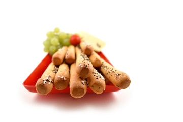 Salty sticks with garnish stock images. Salty sticks on a white background. Salty snack on a red tray. Big salty sticks