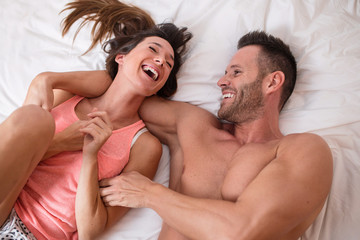 Cheerful couple lying on bed