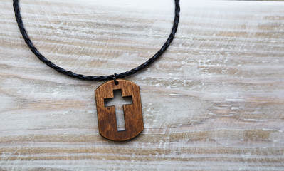 The cross-shaped pendant on the wooden desk