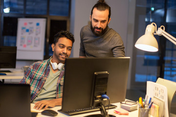creative team with computer working late at office