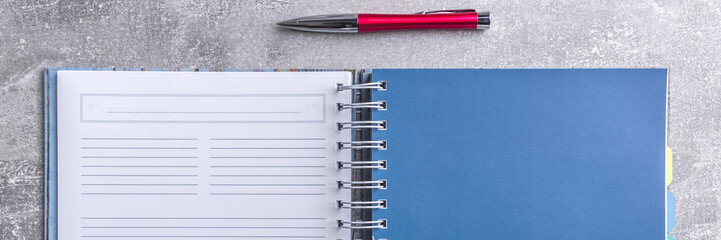 Panoramic view of gray concrete desk top with a notebook with white blank pages and a red elegant pen