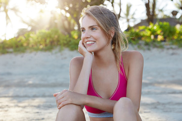 Attractive female jogger or athlete has workout at beach, rests outside, admires sunshine, looks with pleasant smile aside. Happy fitness young woman dressed in pink sport top, poses outdoors.