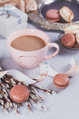 Pink coffee mug with sweet pastel french macaroons, gift box and pussy willow