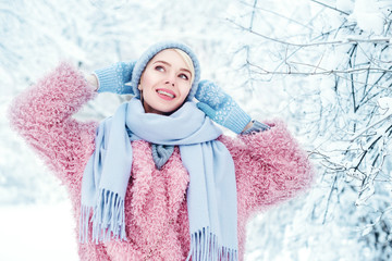 Outdoor portrait of young beautiful happy smiling girl posing in winter park, wearing stylish pink faux fur coat, blue scarf, beanie hat, gloves. Model with braces on her teeth. Copy, empty space