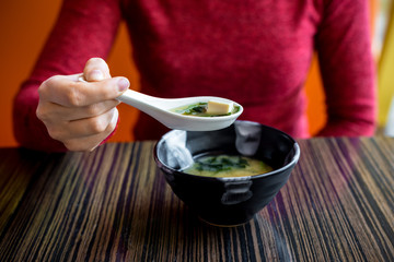 Plate with miso soup at the table.