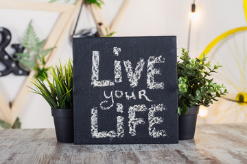 Black board with motivational inscription on the table. Live your life.