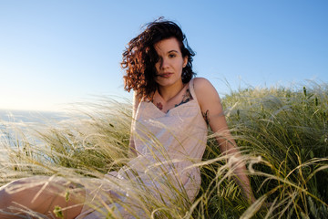 Outdoor fashion portrait of young beautiful brunette woman with tattoo. Pretty sensual girl on nature on grass on background of sea. copy space