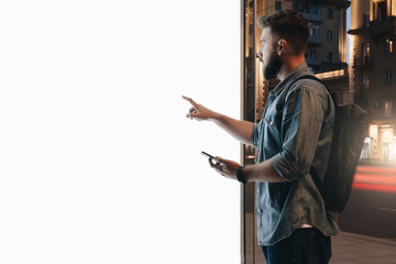 Summer night. Young hipster bearded man stands on city street and touches large glowing touchscreen while holding smartphone. Innovative technologies, digital display, urban navigation. Mock up. Wall mural