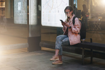 Summer night. Young woman in eyeglasses with backpack is sitting at bus stop and is using smartphone. Hipster girl writes message, chatting, browsing internet, checking email. Social media, network.