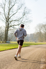 Man running on a asphalt path in the Amsterdamse Bos.