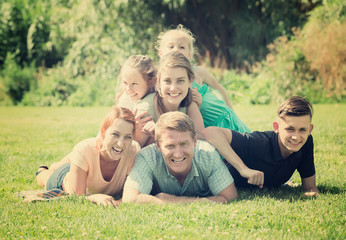 Portrait of big vigorous family lying together on green lawn outdoors