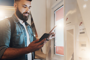 Summer night. Young hipster man with beard stands on city street and touches digital display while looks on screen of smartphone. Innovative technologies, digital display, urban navigation. Mock up.