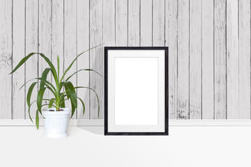 Photo frame mockup and Yucca plant in flower pot near wooden  wall