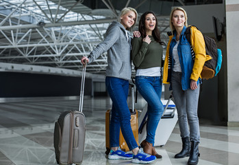 Young girls looking aside with joy while standing at the airport hall with baggage. Copy space in left side