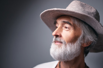 Middle aged traveler. Studio portrait of handsome senior man with gray beard and hat.