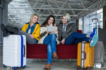 Pleasant awaiting. Company of three girls sitting on couch in the terminal hall. They are looking at tablet with satisfaction