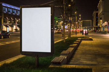Vertical blank glowing billboard on night city street. In background buildings and road with cars. Mock up. Light box on street next to roadway. Space for logo, text, image, advertising, ad, blurb. Fotomurales